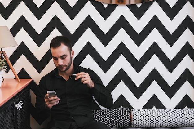 Kerel die eerste ochtendkoffie drinkt terwijl het controleren van e-mail op mobiel