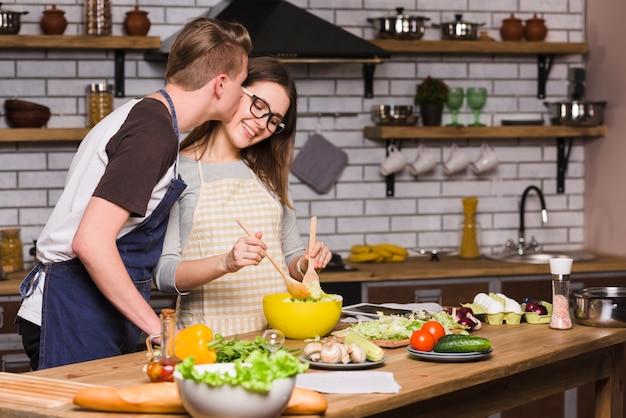 Kerel die jonge vrouw kust die salade in keuken mengt