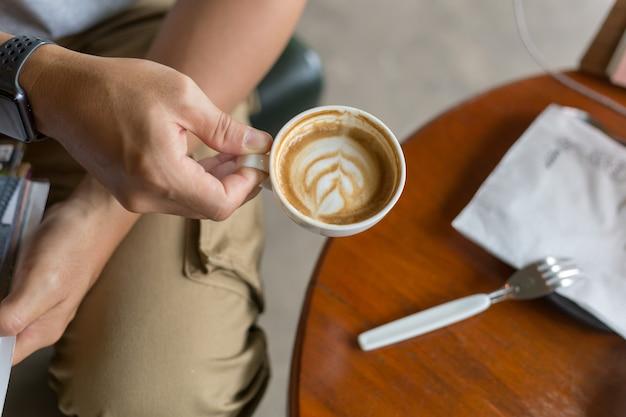 Kerel die ladingsbroek draagt en een koffie in koffiewinkel drinkt