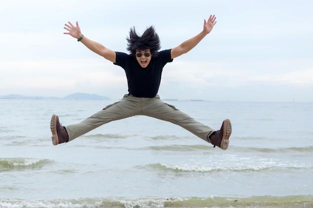 Kerel die ladingsbroek draagt en zich op het strand bevindt