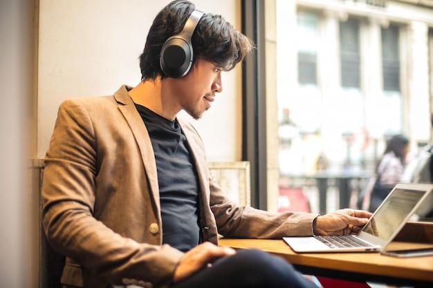 Kerel die met zijn laptop werkt, naar iets luistert
