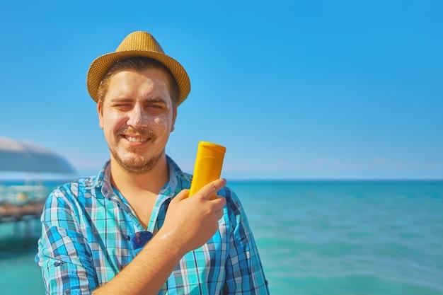 Kerel die op de room van de zonbescherming op het gezicht zet.