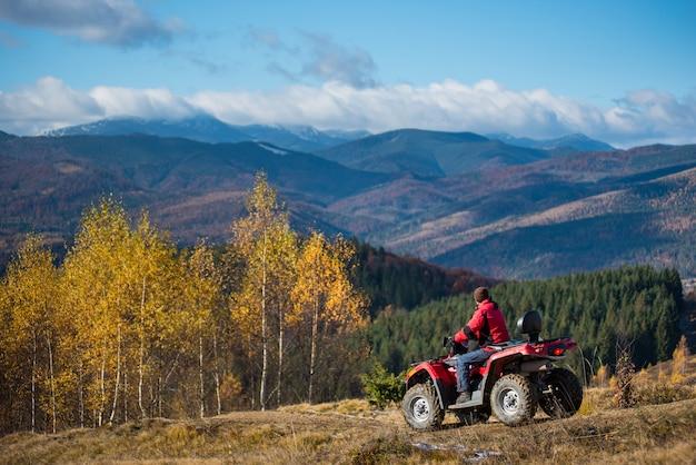 Kerel die op een atv op de heuvelige weg op een achtergrond van bergen, bos en blauwe hemel in de herfst berijdt