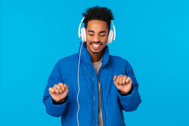 Kerel die positieve vibes opvangt, zich groovie voelt en tevreden met nieuwe koptelefoons vrolijke afrikaanse ameri...