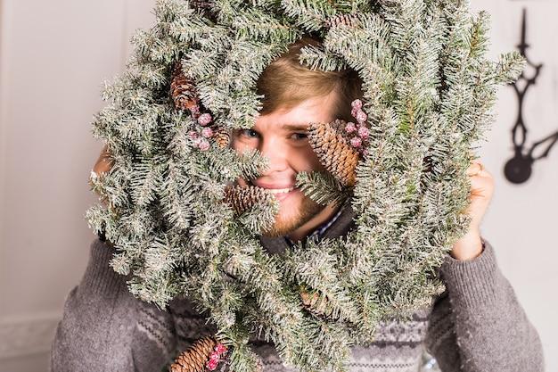 Kerel die pret heeft op feestje. man met een kerstkrans op zijn gezicht