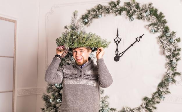 Kerel die pret heeft op feestje. man met een kerstkrans op zijn hoofd.