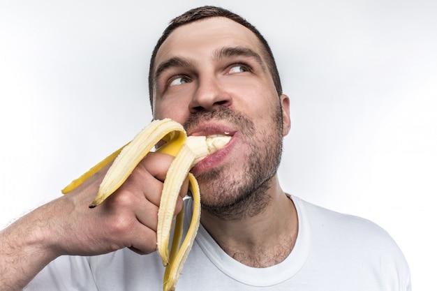 Kerel die rijpe banaan eet die op witte achtergrond wordt geïsoleerd