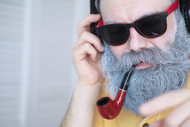 Kerel die tabakspijp rookt. hipster met grijze baard en snor. slechte gewoonten