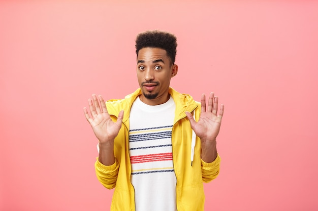 Kerel die uit de problemen blijft. portret van een verwarde, onzekere afro-amerikaanse man met baard die handpalmen opheft in overgave, onschuldig starend naar de camera en ontkennend dat alles niet betrokken is.
