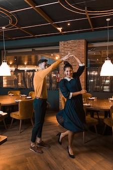 Kerel die vrolijke dame in restaurant wervelt