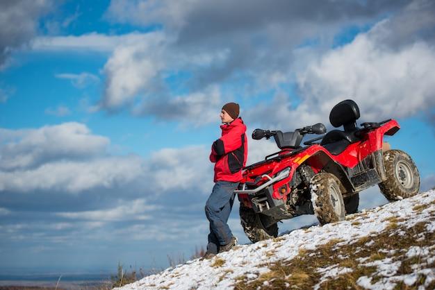 Kerel die zich dichtbij rode atv-vierlingfiets bevinden op sneeuwberghelling