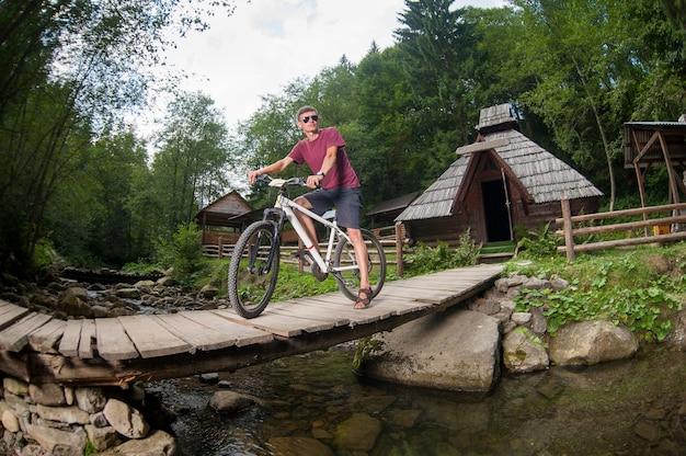 Kerel die zich op de brug over de rivier met fiets bevindt