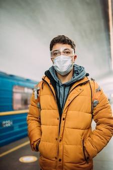 Kerel die zich op station in medisch beschermend masker op zijn gezicht bevindt