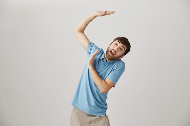 Kerel die zijn handen boven het hoofd opheft, probeert iets zwaars vast te houden
