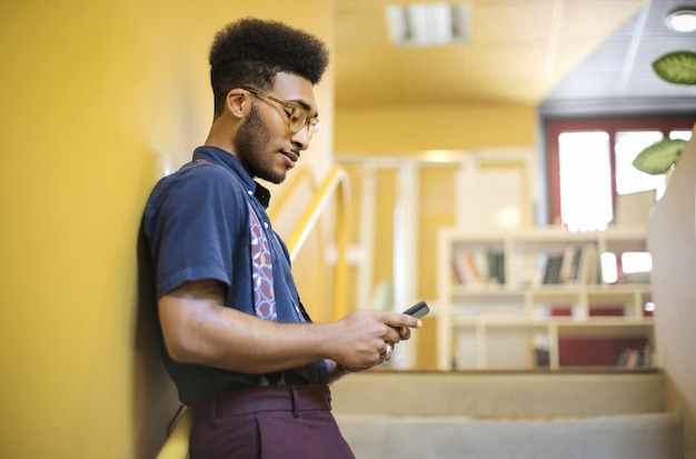 Kerel die zijn slimme telefoon controleert, die zich op de treden bevindt