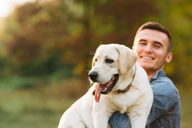 Kerel die zijn vriendhond labrador houdt en bij zonsondergang glimlacht