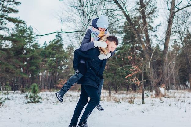 Kerel die zijn vriendin op de rug in de winterbos geeft. jong houdend van paar dat pret heeft in openlucht
