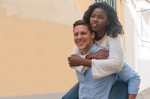 Kerel die zwart meisje op rug in stad vervoeren