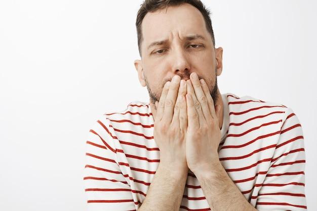 Kerel drinkt veel alcohol, voelt een kater en maagklachten. portret van zieke grappige kerel in vrijetijdskleding, die mond behandelt met handpalmen