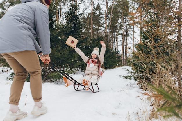 Kerel heeft plezier met het sleeën van zijn vriendin met cadeaus in een winternaaldbos