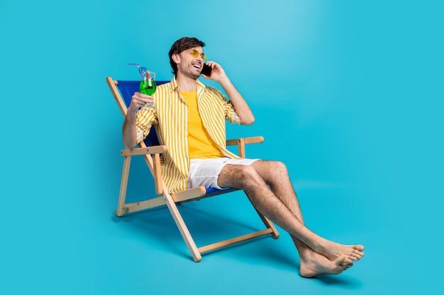 Kerel ik paradijs. volledige lengte foto man ontspannen rust resort zitten chaise-lounge drinken cocktail bellen vriend vertellen weekend dragen wit geel shirt korte broek blootsvoets geïsoleerd blauwe kleur achtergrond