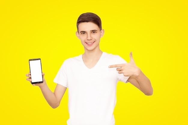 Kerel in een wit t-shirt adverteert de telefoon, geïsoleerd op een gele achtergrond