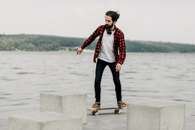 Kerel in flanel op skateboard door een meer