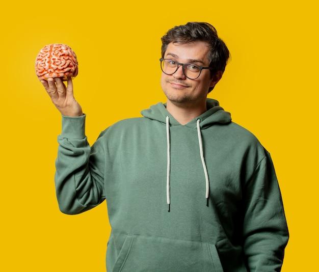 Kerel in groene hoodie met hersenen op geel