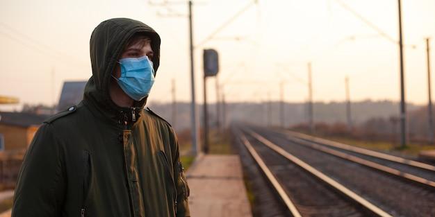 Kerel in wegwerp medisch masker dat zich bij station op zonsondergang bevindt.