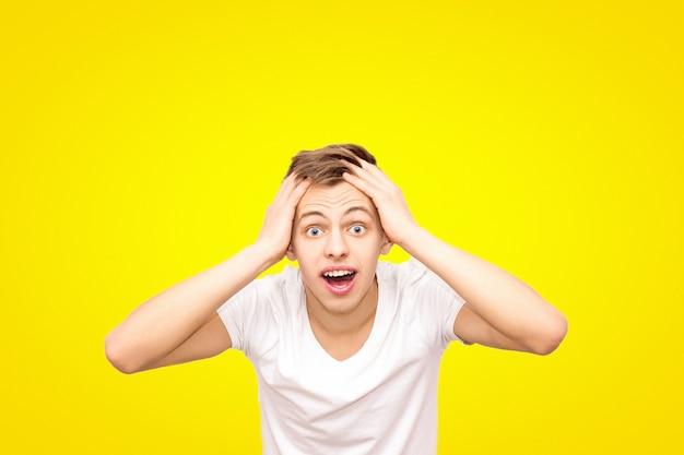 Kerel in wit in een wit t-shirt houdt zijn hoofd, geïsoleerd op een gele achtergrond