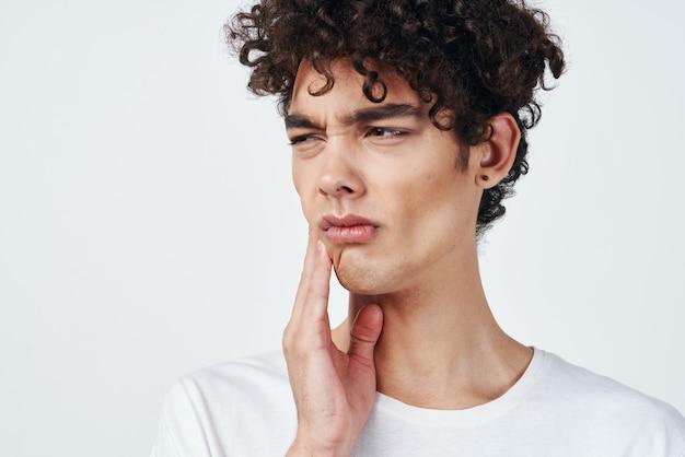 Kerel in witte t-shirt met krullend haar pijn in de tanden gezondheidsproblemen