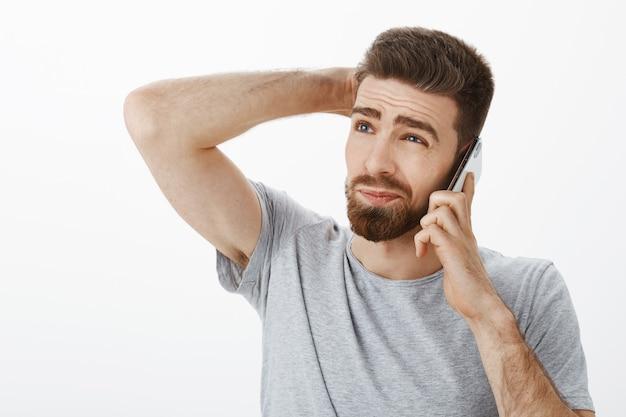 Kerel intens, onhandig probeert nee te zeggen tijdens een telefoongesprek. onzeker aarzelend knappe vriendje met baard en zieke wenkbrauwen krabben achterhoofd omhoog staren met mobieltje bij oor beslissen hoe antwoord