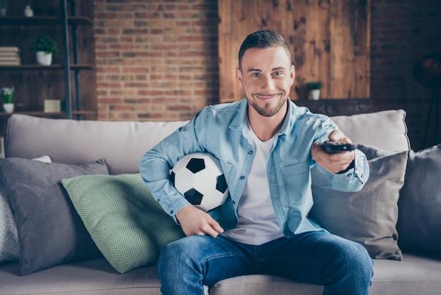 Kerel kijken voetbalwedstrijd hold bal afstandsbediening