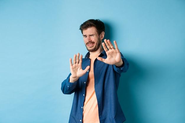 Kerel krimpt ineen van iets walgelijks of gênants, strekt zijn handen uit en vraagt om te stoppen, ontevreden grijnzend, staande op een blauwe achtergrond.