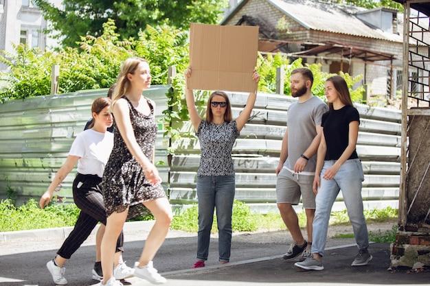 Kerel met bord - vrouw staat te protesteren tegen dingen die haar irriteren. solodemonstratie haar recht om vrij te praten op straat met bord. copyspace voor tekst. mening gehoord door het publiek. sociaal leven, humor, meme
