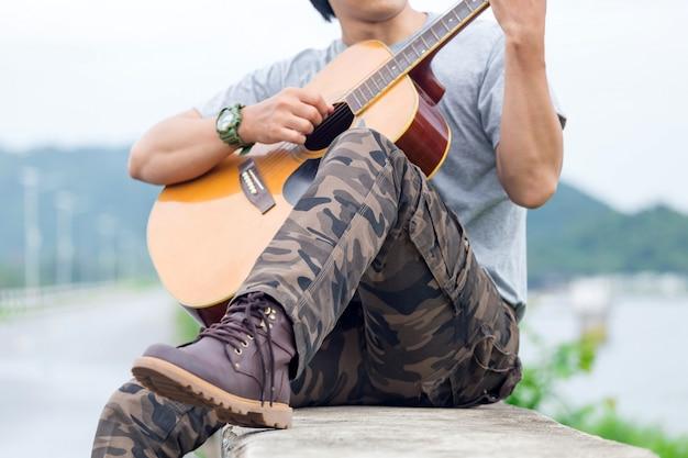 Kerel met gitaar die zich op de dam, ladingsbroek bevindt