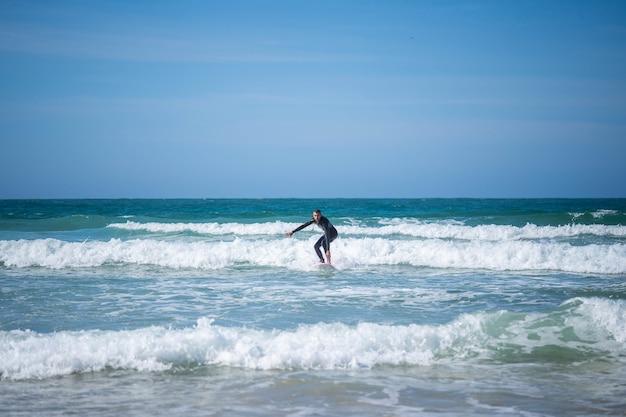 Kerel op een surfplank op gebogen benen. concept: balans, stabiliteit, coördinatie