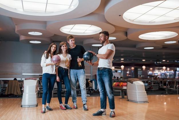 Kerel praat over iets. jonge, vrolijke vrienden vermaken zich in het weekend in de bowlingclub