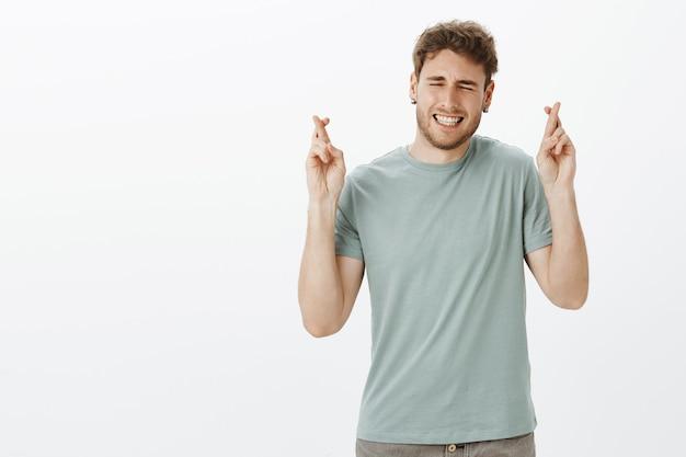 Kerel wil een droom die uitkomt met heel zijn hart. portret van grappige knappe man in t-shirt, gekruiste vingers opheffen, ogen sluiten en tanden op elkaar klemmen tijdens het maken van wensen of bidden