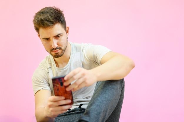 Kerel zat op de vloer met behulp van smartphone, op roze pastelkleurachtergrond.