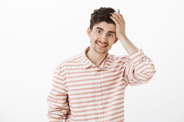 Kerel zegt sorry en geeft zijn fout toe. portret van beschaamd onzeker aantrekkelijk mannelijk model met baard en snor, haar aanraken en onhandig glimlachen, vergeetachtig of verlegen zijn over grijze muur