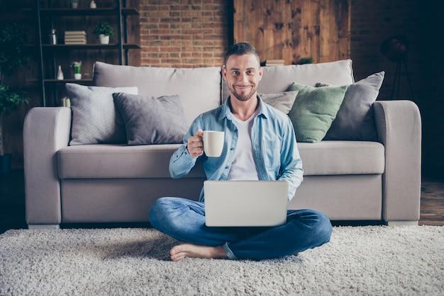 Kerel zittend tapijt in de buurt van bank drinken hete koffie browsen notebook