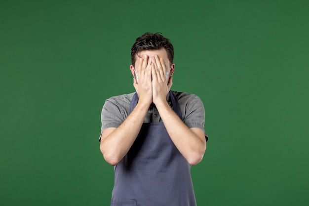 Kerelkelner in uniform met medisch masker dat zijn gezicht sluit met handen op groene achtergrond