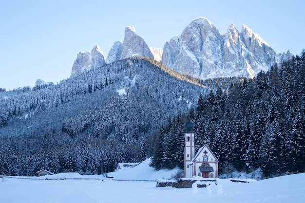 Kerk in besneeuwde bossen onder de bergen van de dolomieten