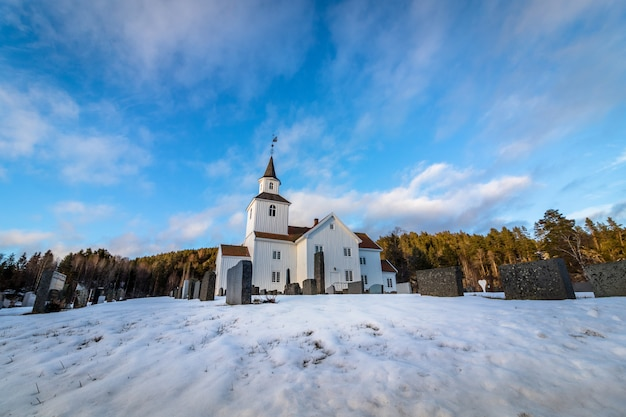 Kerk in de winter met sneeuw en blauwe hemel in iveland noorwegen