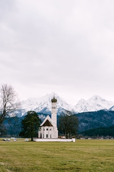 Kerk st coloman in duitsland in beieren dichtbij kasteel neuschwanstein met uitzicht op de besneeuwde toppen