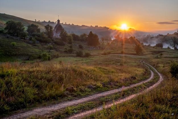 Kerk van de aartsengel mikhail zon met stralen mistige ochtend kocherginka dorp russia