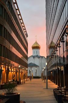 Kerk van st. nicholas the wonderworker onder glazen kantoorgebouwen, kerk tussen glazen kantoorgebouwen bij zonsondergang
