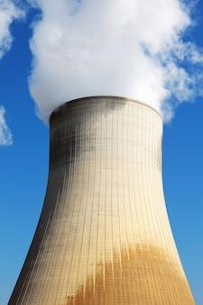 Kerncentrale koeltoren in blauwe hemel