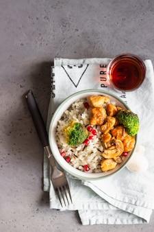 Kerrie kip met rijst, champignon en broccoli versierd met granaatappel zaden